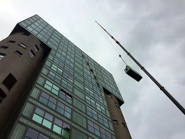 Ein INMESOL IV-110 Stromaggregat wird auf die Dachterrasse des Gebäudes gehoben.