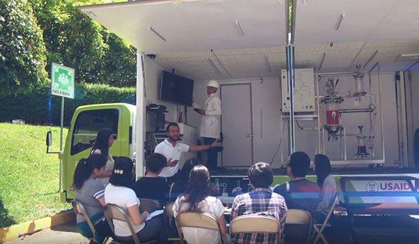 """Schüler hören im """"Steam Truck"""" der Erklärung über die Herstellung von Biodiesel zu"""